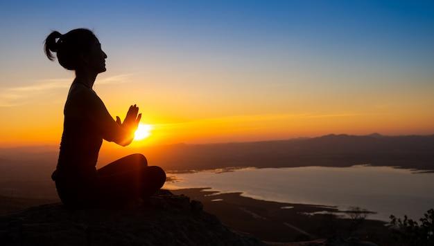 Silhouette yoga sulla montagna