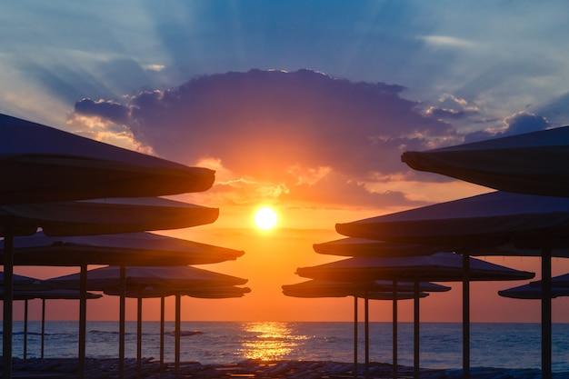 Silhuettes di ombrelloni su una spiaggia deserta in serata su uno sfondo tramonto