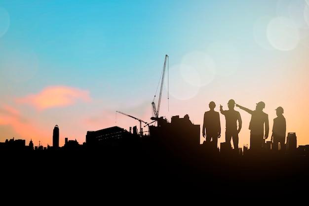 Sillouette dell'ingegnere e del gruppo edile che pianifica e indaga lo spazio di costruzione