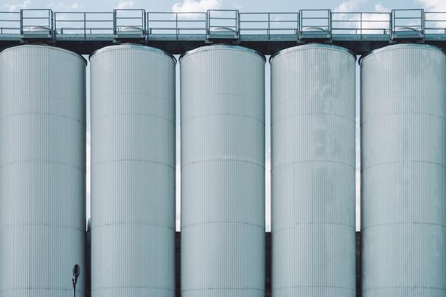 Silos agricoli. conservazione e essiccazione di cereali, grano, mais, soia, girasole. esterno di un edificio industriale. primo piano di grandi contenitori metallici d'argento. sfondo di carri armati agricoli con spazio di copia.