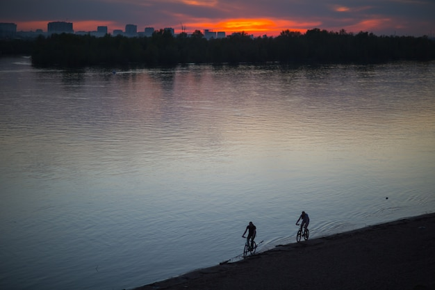 Siluetta dei ciclisti che guidano una bici della strada al tramonto nel fiume della spiaggia