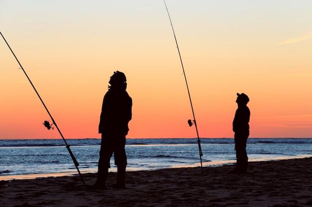 Siluetta dei pescatori sulla spiaggia all'alba