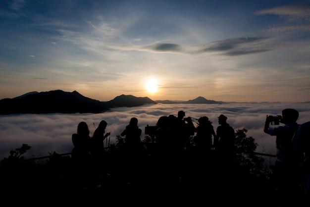 Siluetta dei turisti che esaminano foschia e montagna con il fondo della natura di alba