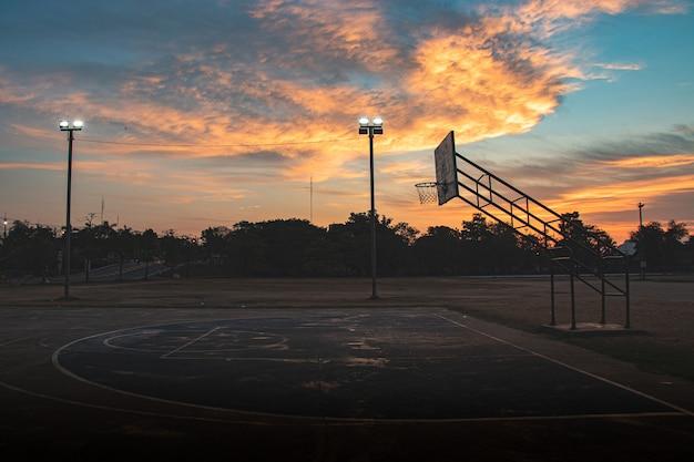 Siluetta del campo da pallacanestro all'aperto con il cielo drammatico nella mattina di alba
