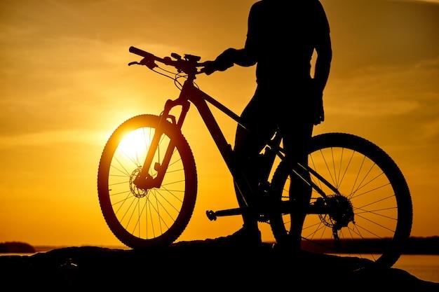 Siluetta del ciclista in mountain-bike nell'alba