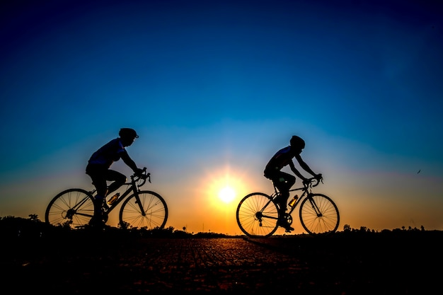Siluetta del ciclista nella priorità bassa di tramonto.