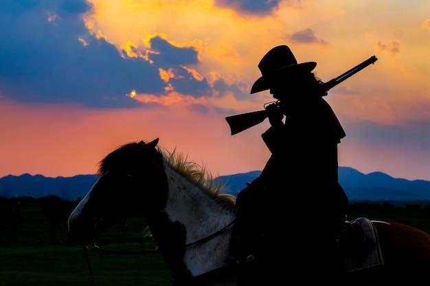 Siluetta del cowboy su un cavallo durante il tramonto piacevole