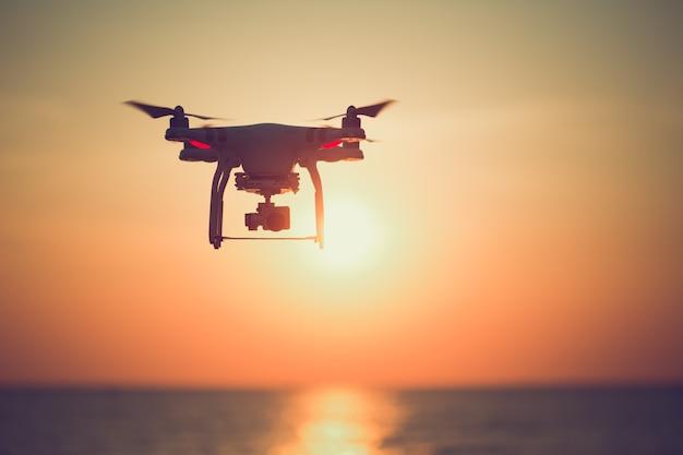 Siluetta del drone che si libra nel bello tramonto sull'oceano.