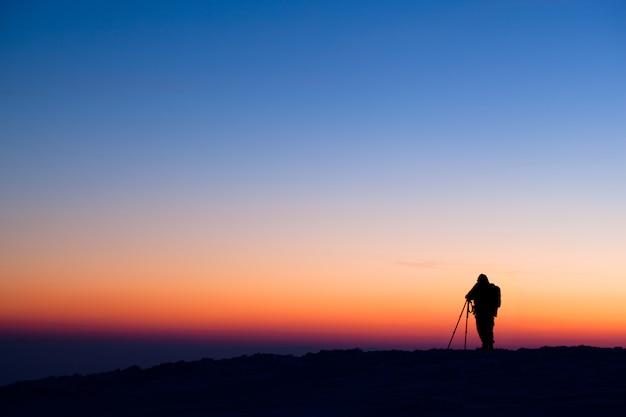 Siluetta del fotografo che sta sulla collina e che fa foto della valle di sera