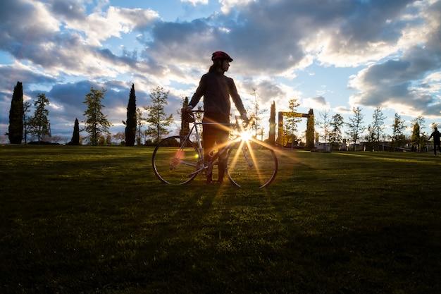Siluetta del giovane che sta con la bicicletta in parco sul tramonto