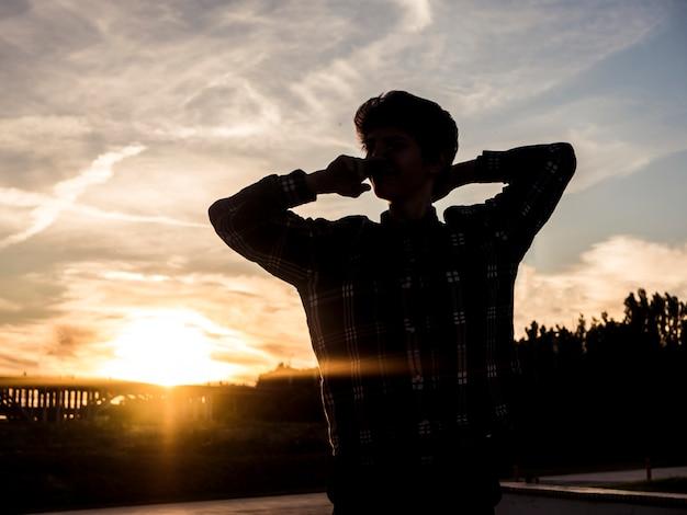 Siluetta del giovane con le mani dietro la testa che sogna fuori durante il tramonto