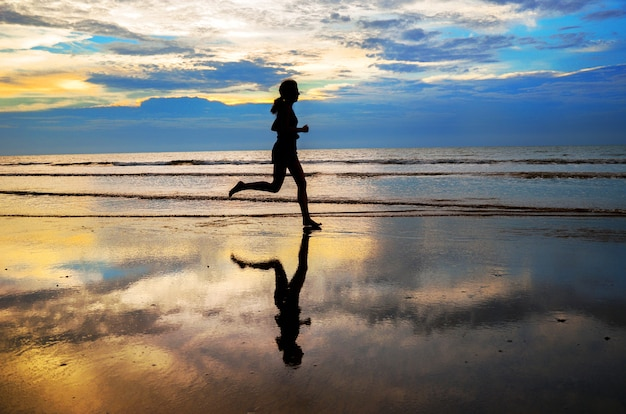 Siluetta del pareggiatore della donna che funziona sulla spiaggia di tramonto, sulla forma fisica e sul concetto di vita sana
