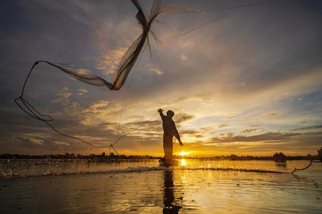Siluetta del pescatore sul peschereccio con rete sul lago al tramonto, tailandia