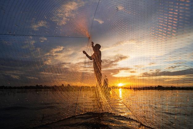 Siluetta del pescatore sul peschereccio con rete sul lago al tramonto