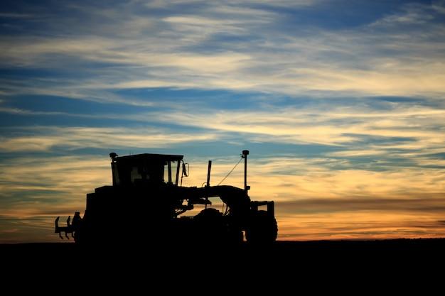 Siluetta del trattore del roadgrader di tramonto della costruzione