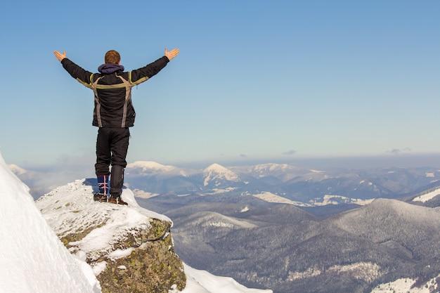 Siluetta del turista da solo in piedi sulla cima della montagna innevata
