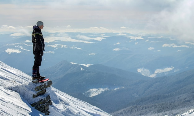 Siluetta del turista solo che sta sulla cima della montagna nevosa che gode della vista e del risultato il giorno di inverno soleggiato luminoso. avventura, attività all'aria aperta e concetto di stile di vita sano.