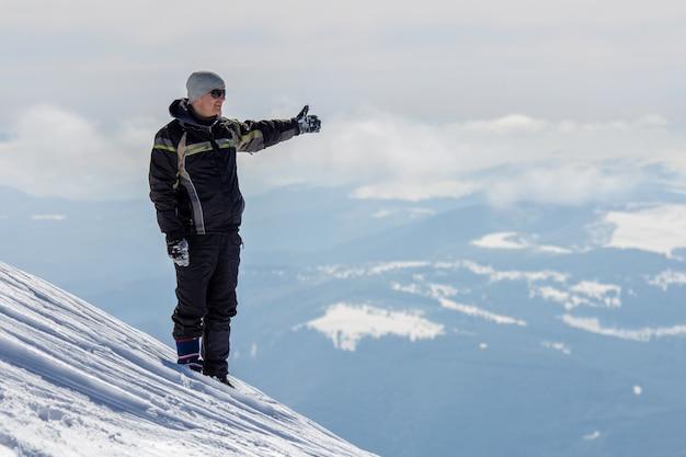 Siluetta del turista solo che sta sulla cima della montagna nevosa nella posa del vincitore con le mani sollevate che godono della vista e del risultato il giorno di inverno soleggiato luminoso. avventura, attività all'aria aperta, stile di vita sano.