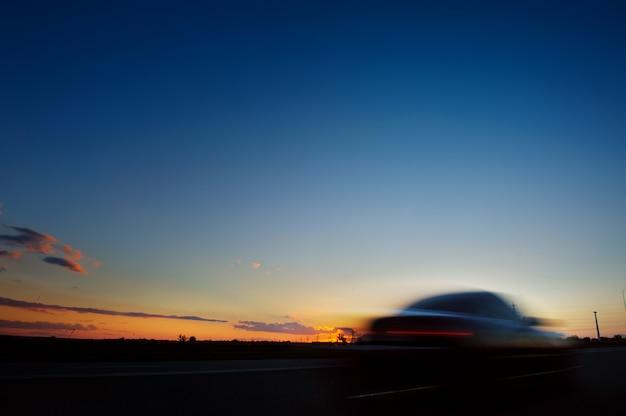Siluetta dell'automobile su backgroun di tramonto