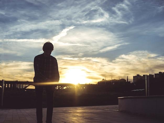 Siluetta dell'uomo che cammina in strada durante il tramonto
