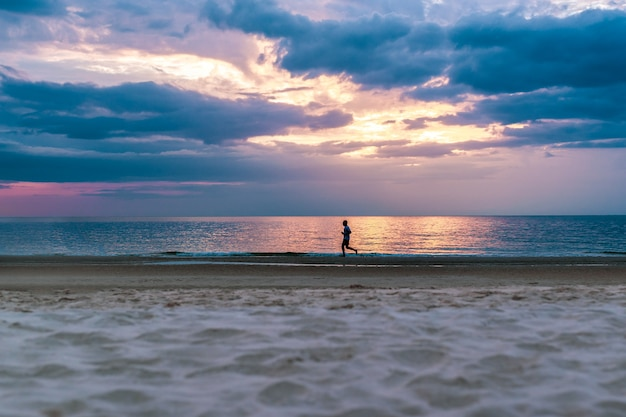 Siluetta dell'uomo che funziona sulla spiaggia al tramonto.