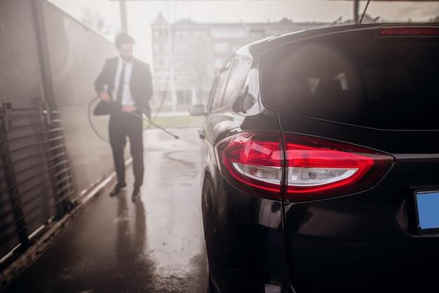 Siluetta dell'uomo che lava la sua automobile nell'autolavaggio.