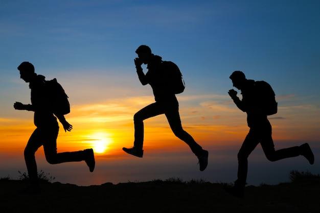 Siluetta dell'uomo corrente contro il cielo variopinto. siluetta dell'uomo corrente sul fondo ardente di tramonto