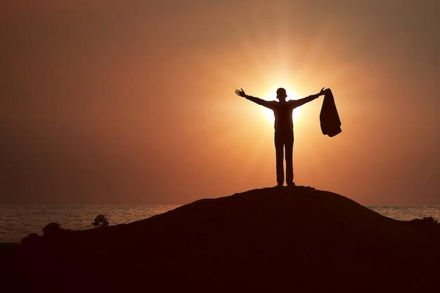 Siluetta dell'uomo d'affari alzato le mani e pregando dio