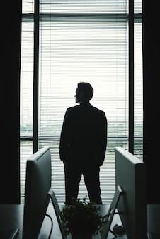 Siluetta dell'uomo d'affari in vestito che sta alla finestra dell'ufficio e che guarda fuori