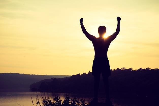 Siluetta dell'uomo di sport del vincitore sulla cima della montagna. sport e concetto di vita attiva