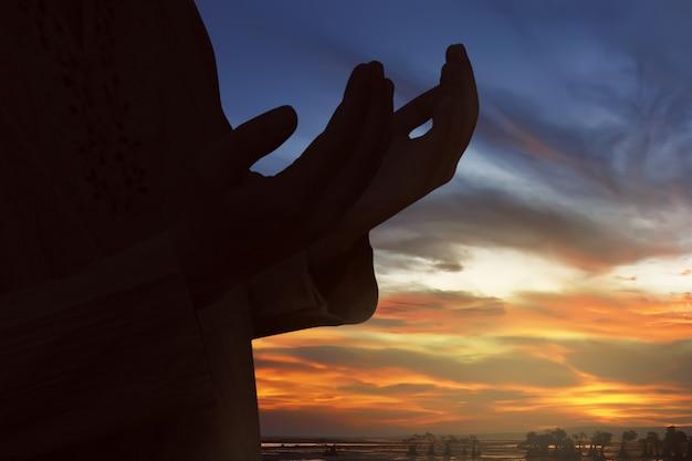 Siluetta dell'uomo musulmano che prega a dio