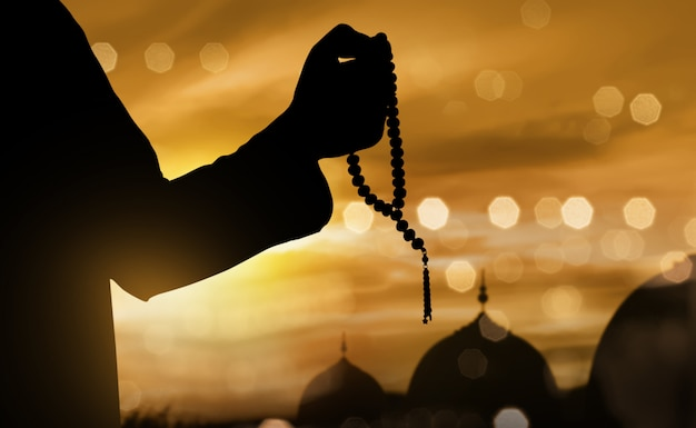 Siluetta dell'uomo musulmano che prega con i branelli di preghiera