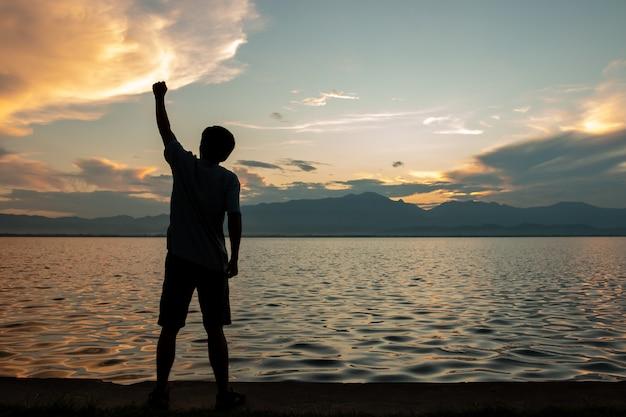 Siluetta dell'uomo sopra il fondo leggero del sole e del cielo