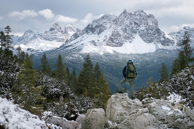 Siluetta dell'uomo sulla cima della montagna sul disegno concettuale del cielo di alba, di sport e di vita attiva.