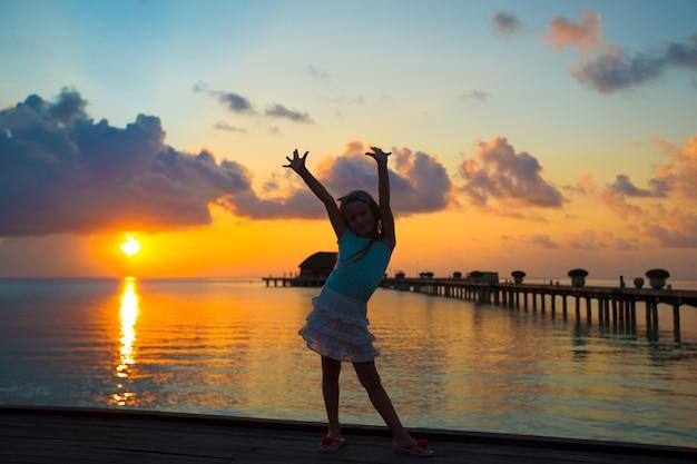Siluetta della bambina adorabile sul molo di legno al tramonto