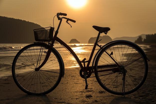 Siluetta della bicicletta alla spiaggia, biciclette sul tramonto della spiaggia o alba