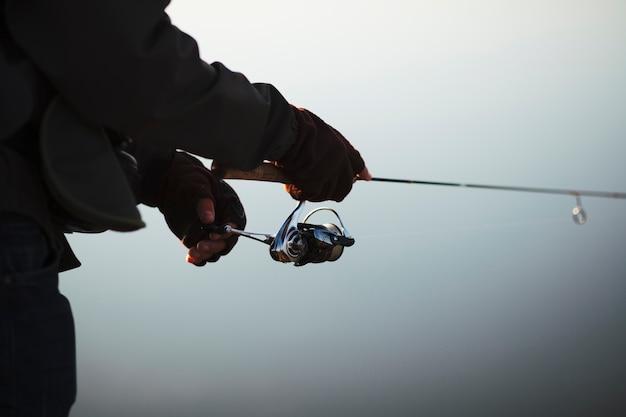 Siluetta della canna da pesca della tenuta della mano di un pescatore
