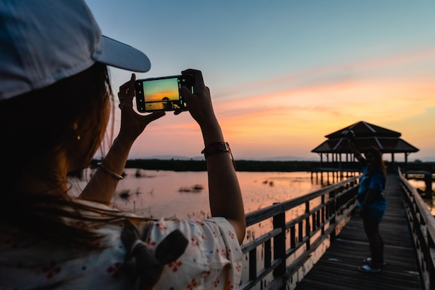 Siluetta della donna che cattura maschera del suo amico che sta sul ponte di legno sul tramonto nel parco nazionale di khao sam roi yot. tailandia.