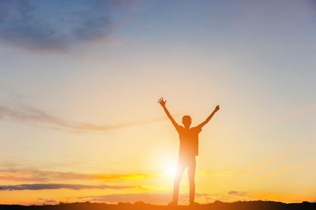 Siluetta della felicità di successo di celebrazione dell'uomo su una cima della montagna fondo di tramonto del cielo di sera.