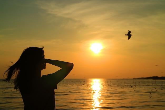 Siluetta della giovane donna che guarda il sole che aumenta sul cielo dorato con un uccello di volo