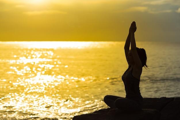 Siluetta della giovane donna che medita e che pratica yoga sulla spiaggia al tramonto.