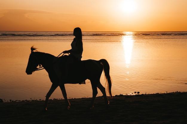 Siluetta della giovane donna che monta a cavallo sulla spiaggia durante il tramonto variopinto dorato vicino al mare