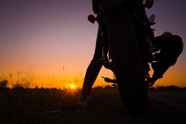 Siluetta della guida della giovane donna con la motocicletta sulla via, godente della libertà e della vita attiva