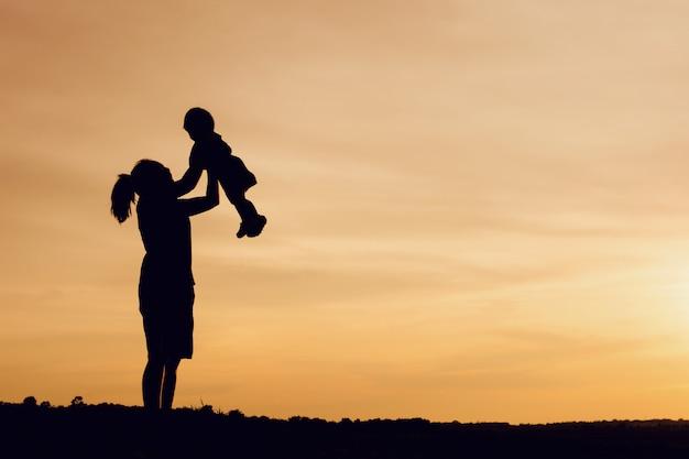 Siluetta della madre e del bambino di sollevamento della figlia in aria sopra il cielo scenico di tramonto alla riva del fiume.