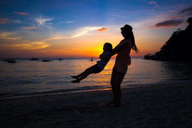 Siluetta della madre e della piccola figlia su boracay, filippine