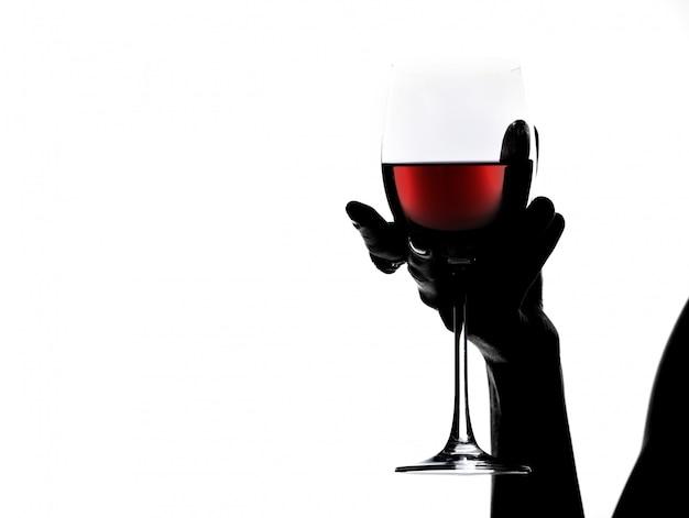 Siluetta della mano della donna del primo piano che tiene un bicchiere di vino.