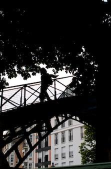 Siluetta della persona che attraversa un ponte a parigi francia
