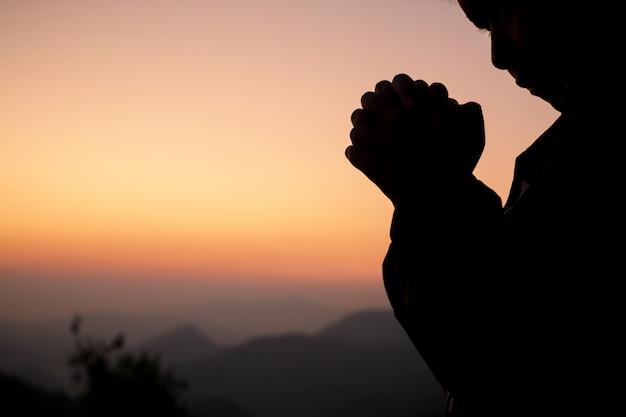 Siluetta della ragazza che prega sopra la bella priorità bassa del cielo.
