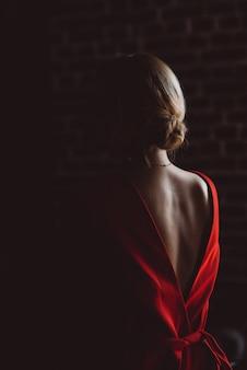 Siluetta della ragazza della signora nella casetta rossa con una parte posteriore aperta nella stanza scura. bellezza e moda.