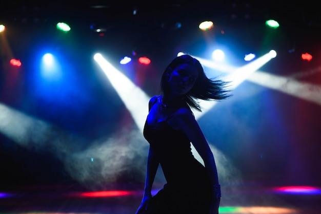 Siluetta della ragazza di dancing contro le luci della discoteca